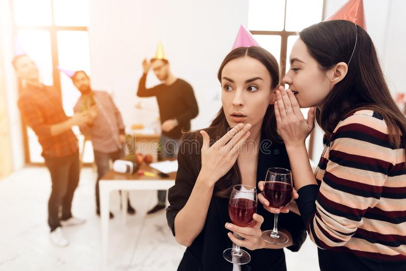 Two girls in festive caps are talking in the office. Their colleagues celebrate a corporate holiday royalty free stock photography