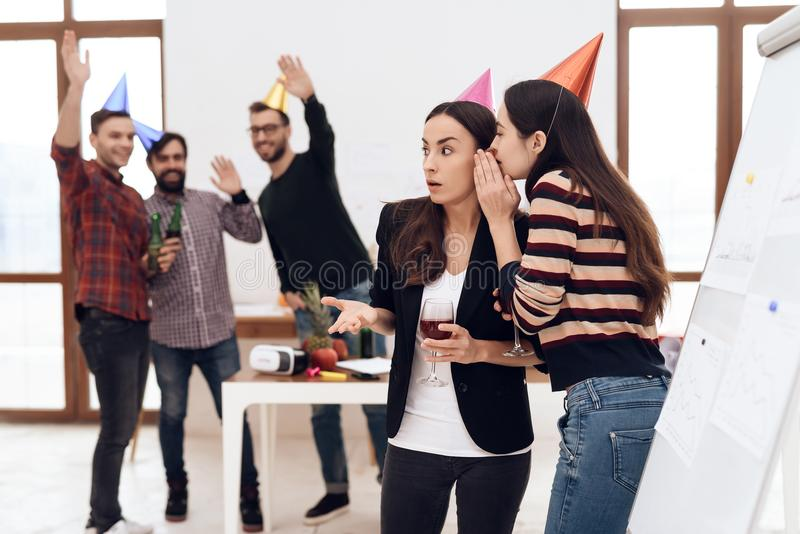 Two girls in festive caps are talking in the office. Their colleagues celebrate a corporate holiday stock images