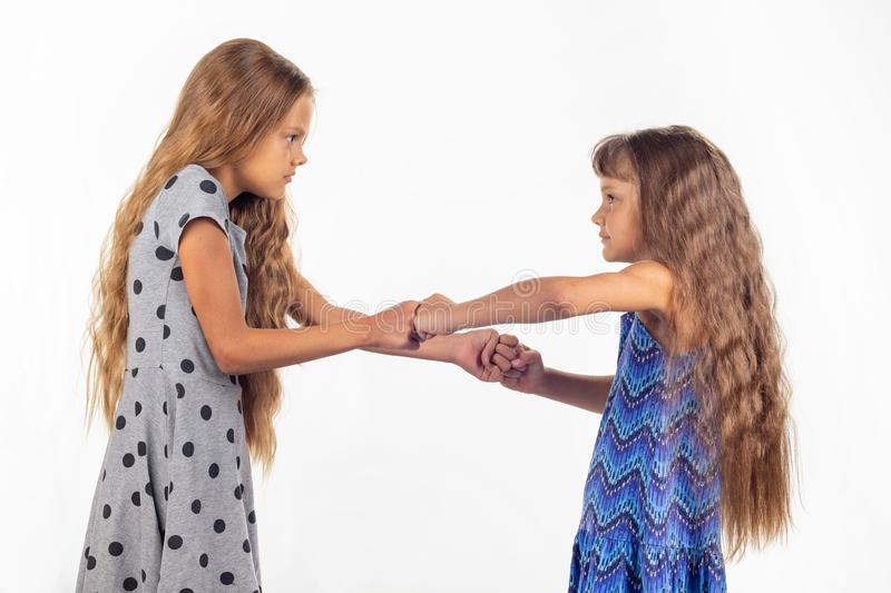 Two girls fight, grabbing each other`s fists. Two girls fight, grabbing each other`s  fists stock photos