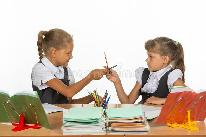 Two girls fight with pencils at a school desk. Two girls fight with pencils at a school  desk stock photos