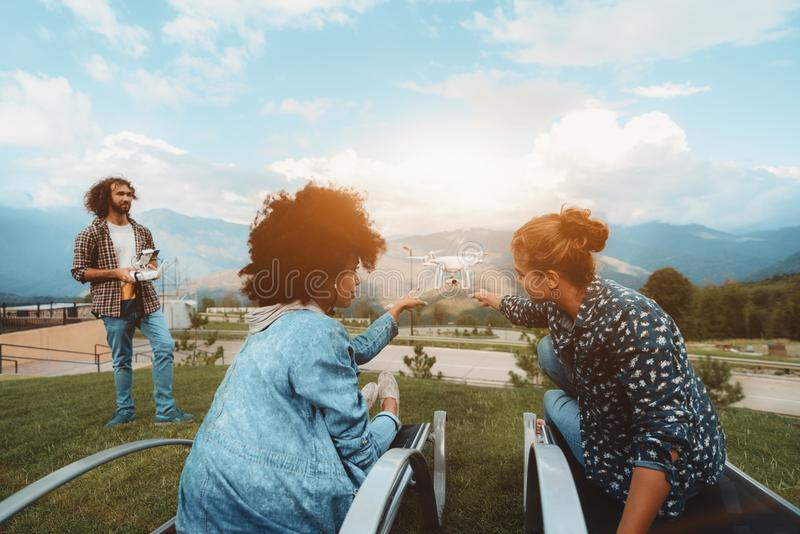 Two girls, flying drone filming them, male operator, mountains b royalty free stock photo