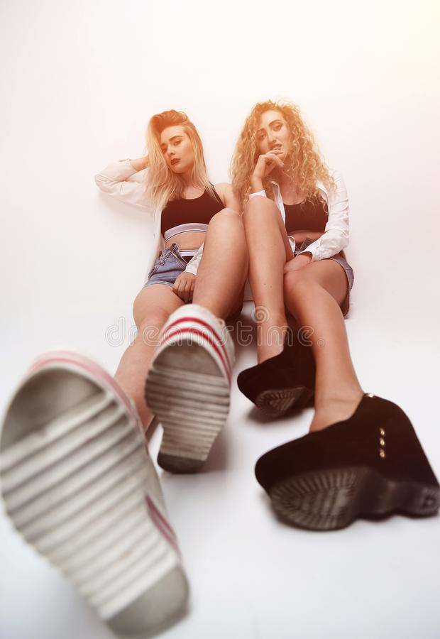 Two girls of a friend sitting next to each other. Stylized image of two girls of a friend sitting next to each other stock image