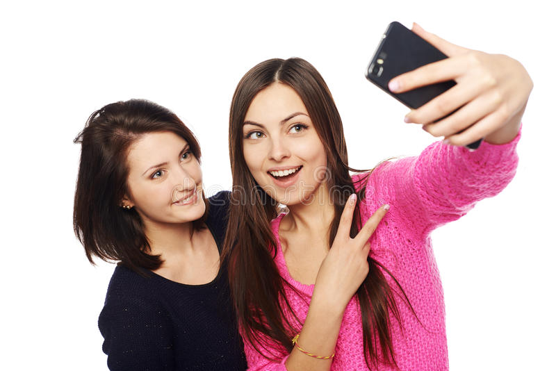 Two girls friends taking selfie with smartphone royalty free stock image