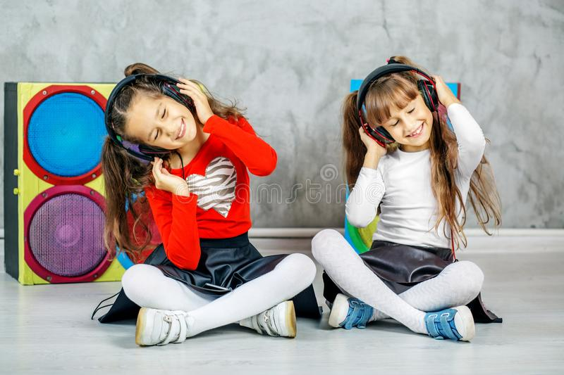 Two girls of the girl dance and listen to the headphones music. stock photos