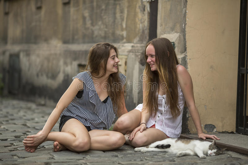 Two girls girlfriend with a cat sitting on the pavement on the street. stock images