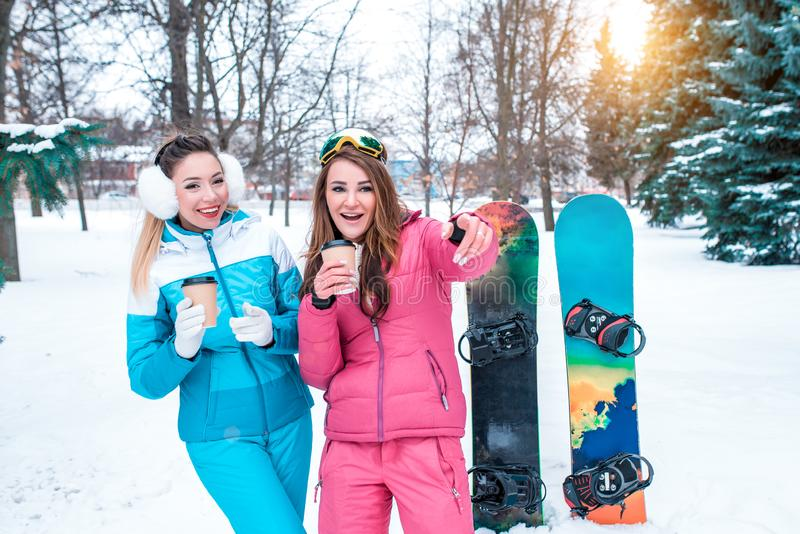 Two girls girlfriends background of snowboards, surprised laughing joke winter park on background of green Christmas stock image