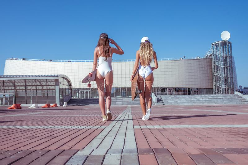 Two girls girlfriends, sisters white body bathing suit, summer city with board, skate longboard. Long hair tanned figure stock photography