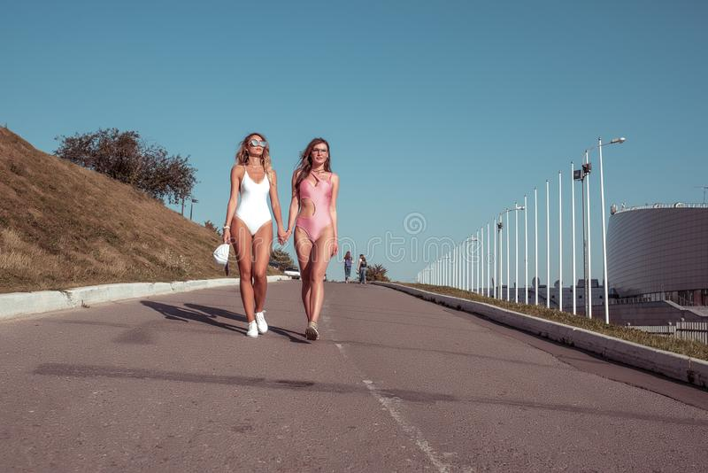 Two girls girlfriends, sisters women walk swimsuits around city, sunbathe. Long hair tanned figure. Concepts fashion. Youth style, trend and fashion modern stock photos