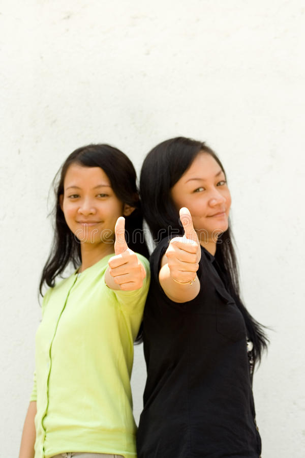 Download Two girls give thumbs up stock photo. Image of together - 12138818