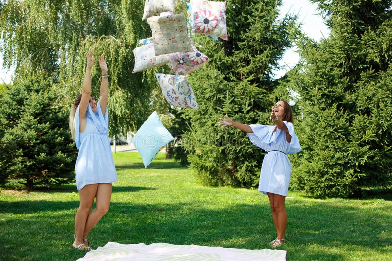 Two girls on a green meadow play throw up pillows while preparing to picnic. Summer weekends royalty free stock photography