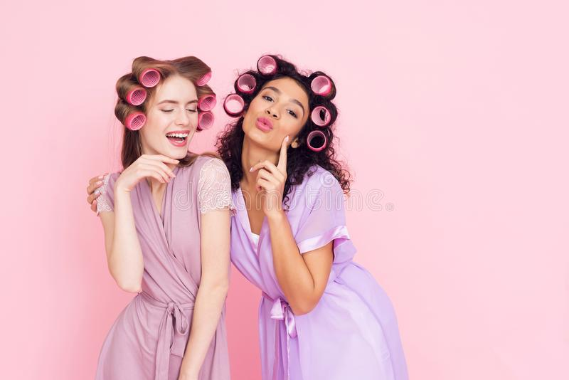 Two girls with hair curlers. They are celebrating women`s day March 8. Two girls in robes with hair curlers. They are celebrating women`s day March 8 royalty free stock photos