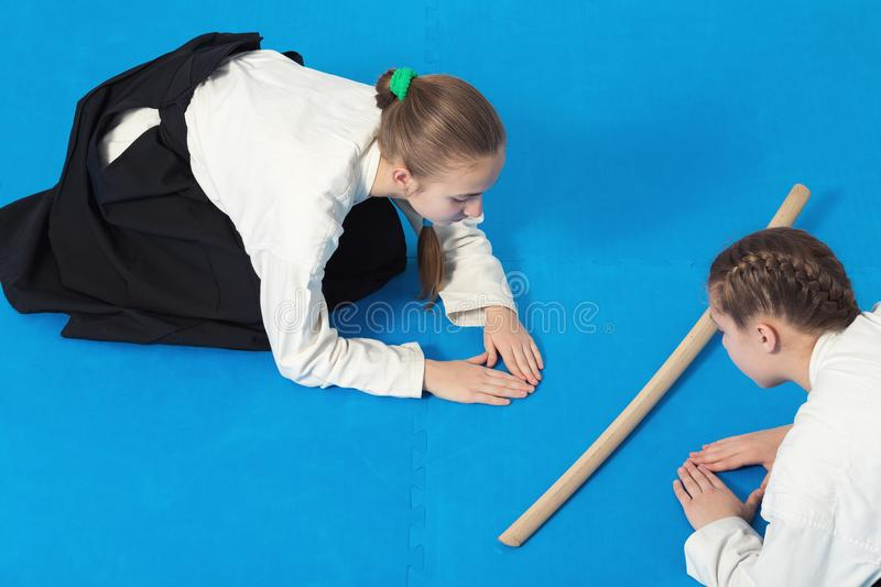 Two girls in hakama bow on Aikido training royalty free stock photos