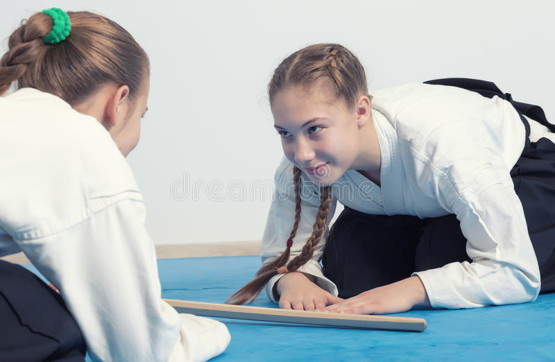 Two girls in hakama bow on Aikido training royalty free stock images
