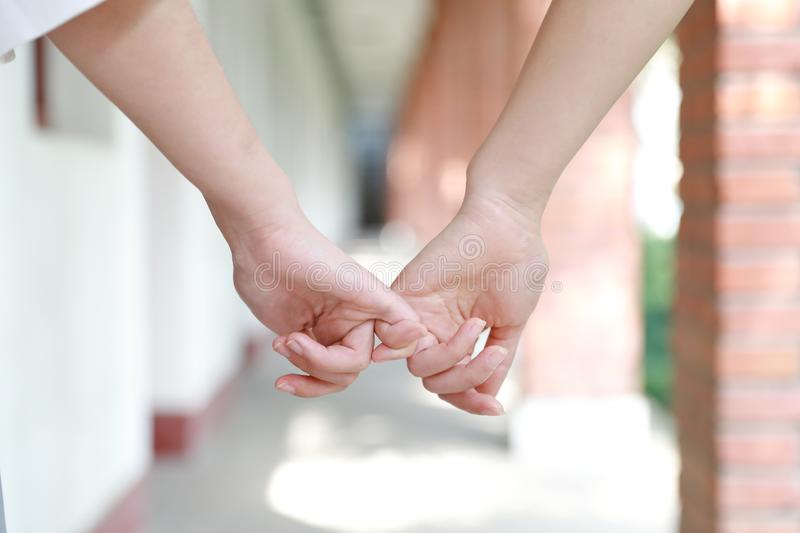 Two girls hand in hand hand close up stand for friendship. Two girls hand in hand hand close up two girls hand in hand in school before classroom at the porch royalty free stock photo