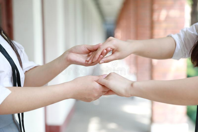 Two girls hand in hand hand close up stand for friendship. Two girls hand in hand hand close up two girls hand in hand in school before classroom at the porch stock photos