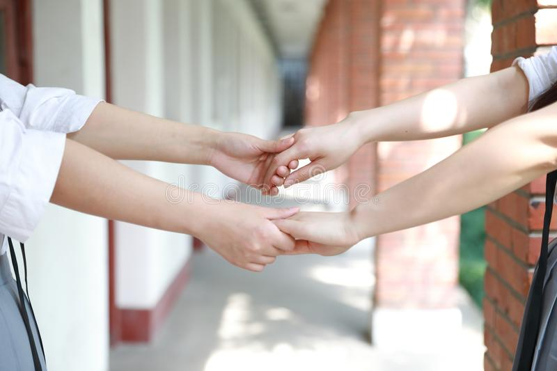 Two girls hand in hand hand close up stand for friendship. Two girls hand in hand hand close up two girls hand in hand in school before classroom at the porch stock photo