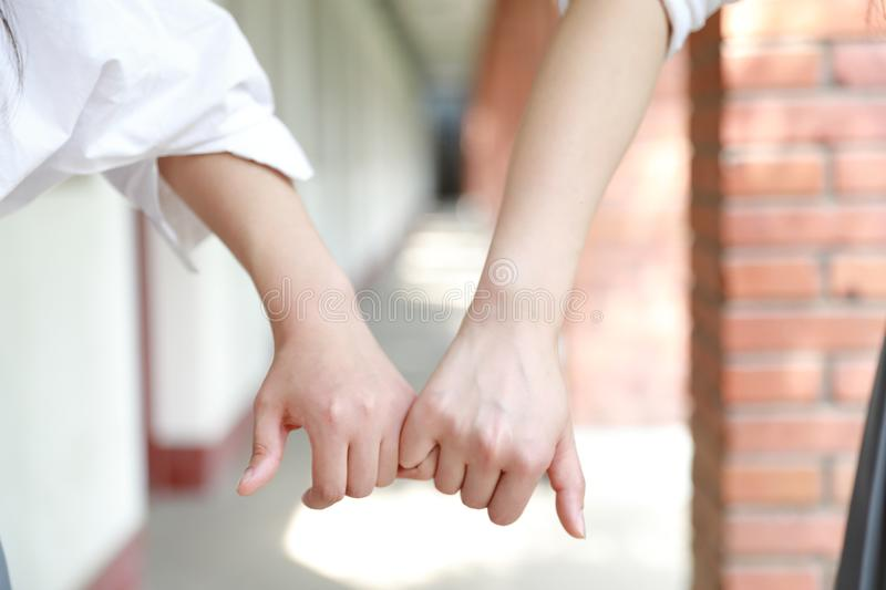 Two girls hand in hand hand close up stand for friendship. Two girls hand in hand hand close up two girls hand in hand in school before classroom at the porch royalty free stock photos