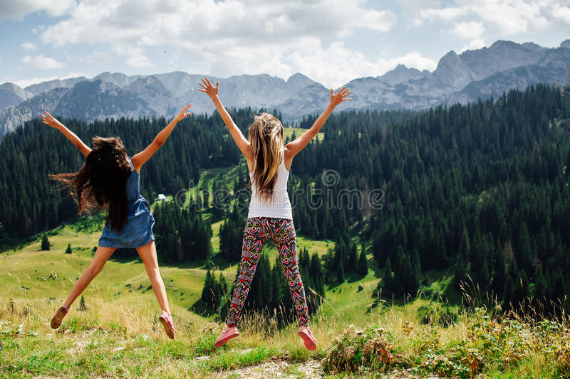 Two girls happy jump in mountains back view stock photography