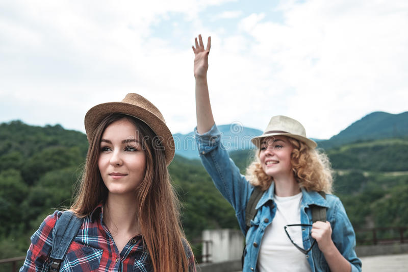 Two girls in hats traveling and hitchhiking royalty free stock photography