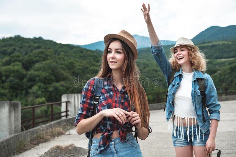 Two girls in hats traveling and hitchhiking. Two girls in cotton hats, tourist backpacks, denim shorts and shirts in a cage travel through modern abandoned ruins stock photo