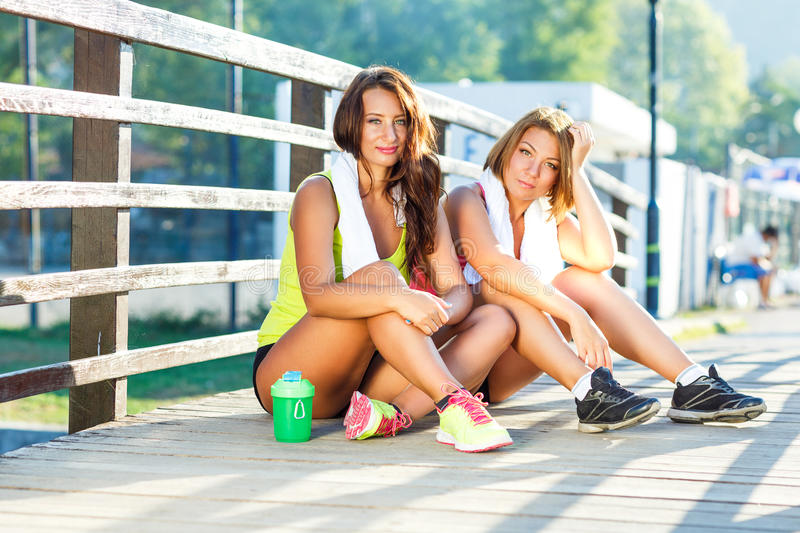 Two girls have a rest after exercising outdoors. Two cute girls have a rest after exercising outdoors stock images