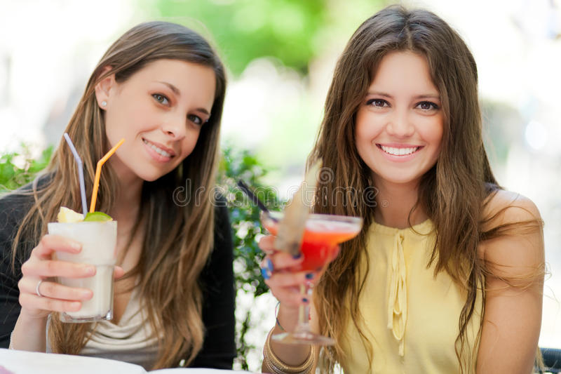 Two girls having an aperitif outdoor stock photography