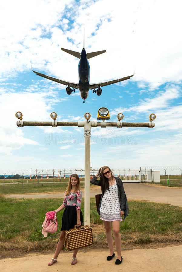 Two girls hitchhiking a plane. Two attractive girls hitchhiking a landing plane on the runway close to an airport wearing summer dresses and carrying lite stock photography