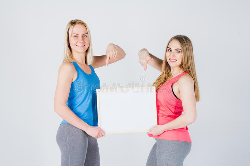 Two girls holding the frame with the ad stock photo