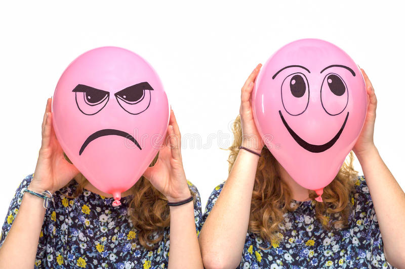 Two girls holding pink balloons with facial expressions royalty free stock image