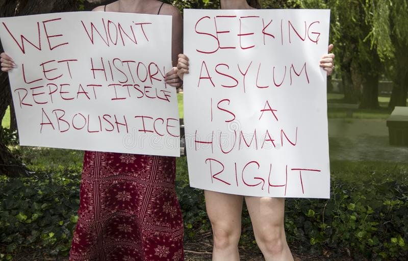Two girls holding signs at immigration protest - We wont let history repeat itself - abolish ice - asylum - cropped and selective. Focus - unrecognizable stock image