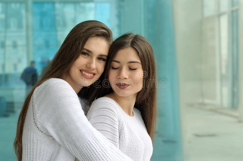 Two girls hug on the background of a glass case royalty free stock image