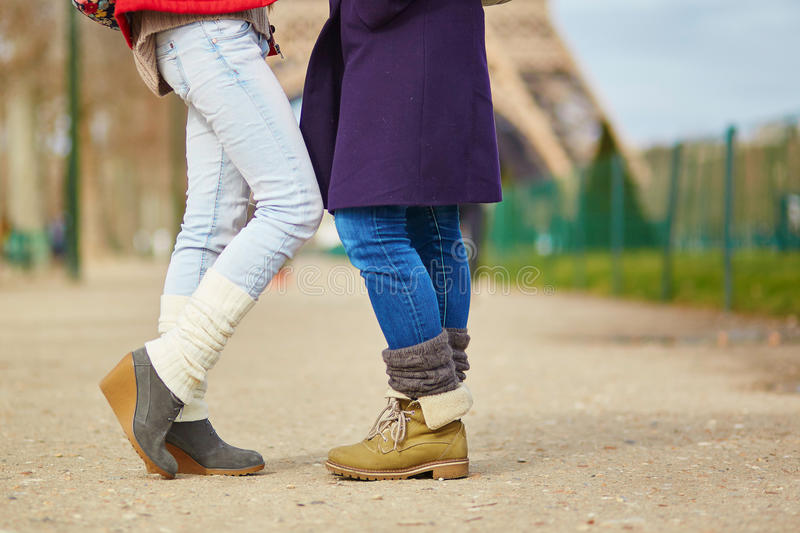 Two girls hugging on the street in Paris. Closeup of female legs, two girls hugging on the street in Paris, same-sex relationship concept royalty free stock images