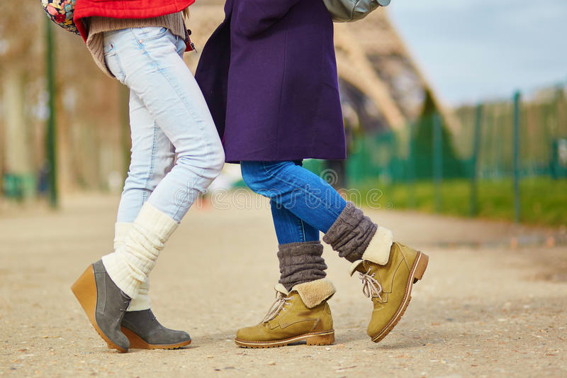 Two girls hugging on the street in Paris. Closeup of female legs, two girls hugging on the street in Paris, same-sex relationship concept stock photography