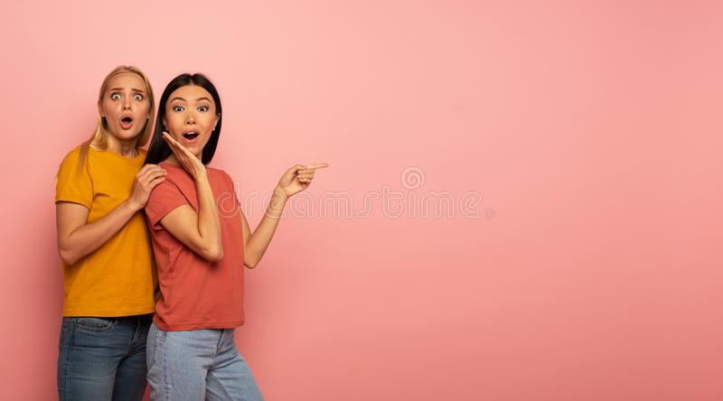 Two girls indicates something. Amazed expression face. Pink background with blank space for your text stock photography