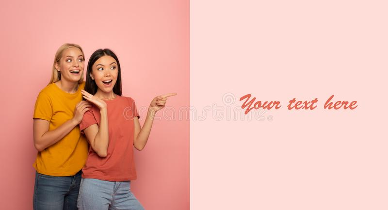 Two girls indicates something. Amazed expression face. Pink background with blank space for your text stock photo