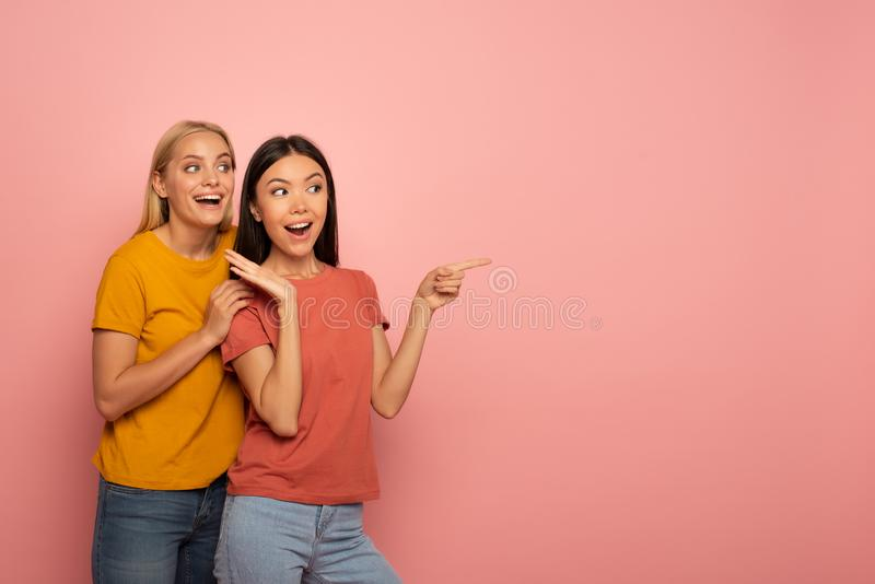 Two girls indicates something. Amazed expression face. Pink background with blank space for your text. Two girls indicates something. Amazed and surprised stock photos