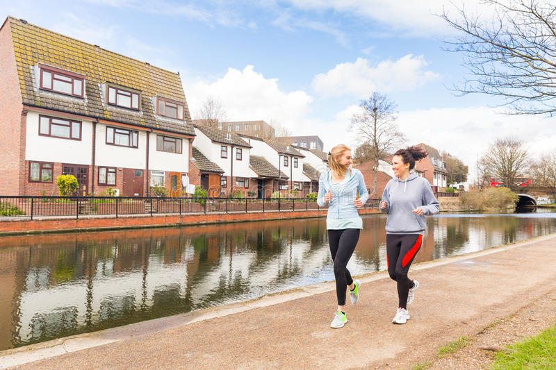 Two girls jogging outdoors in London stock photos