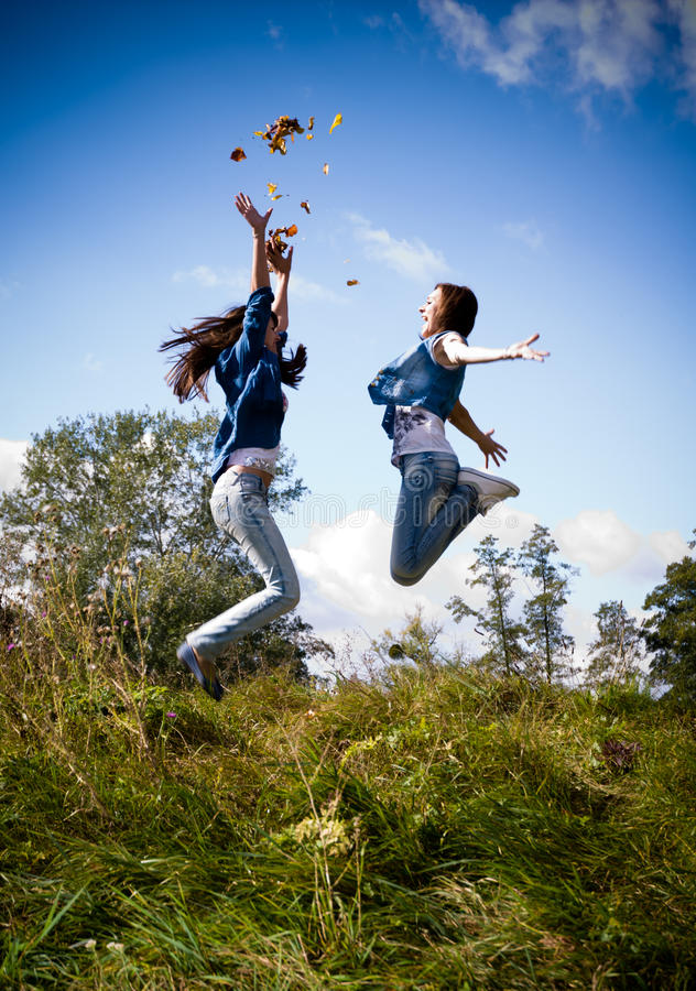 Two girls jumping high excited