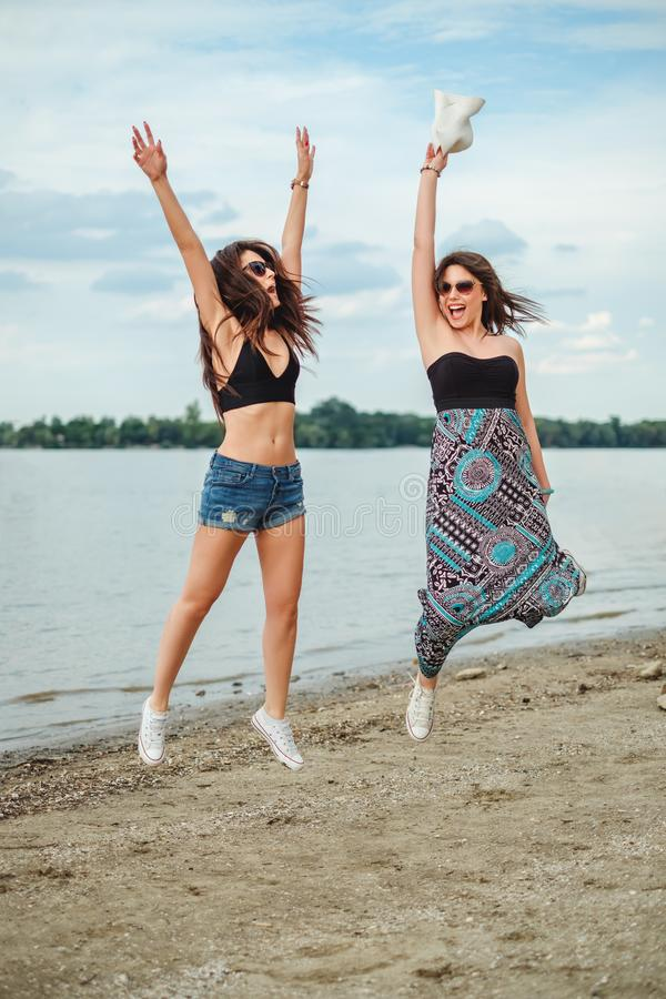 Two girls jumping by the water stock images