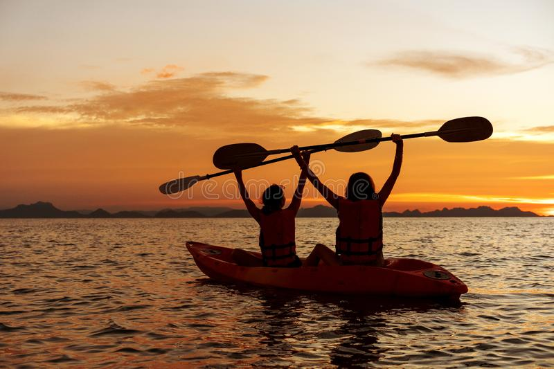Two girls kayaking in the sea at sunset stock image