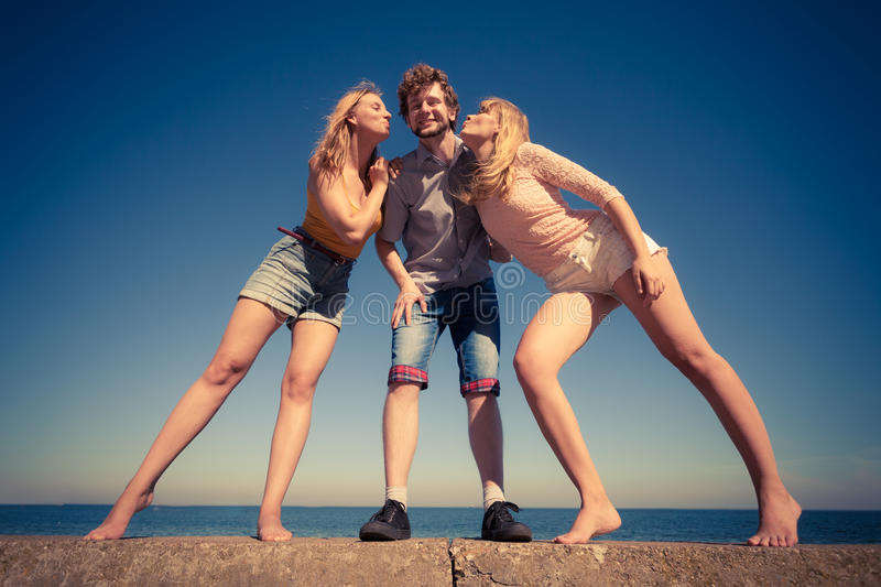 Two girls kissing one boy having fun outdoor. Friendship happiness love concept. Group of friends boy two girls having fun outdoor, women kissing men wide angle stock photo