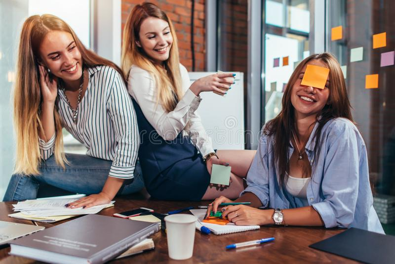 Two girls laughing at their friend with a sticky note on her face. Group of female students relaxing having fun in stock photography