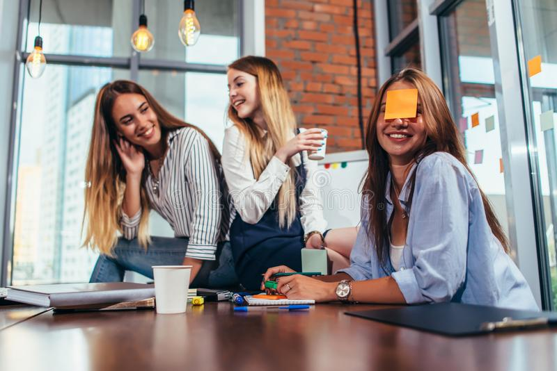 Two girls laughing at their friend with a sticky note on her face. Group of female students relaxing having fun in royalty free stock photo