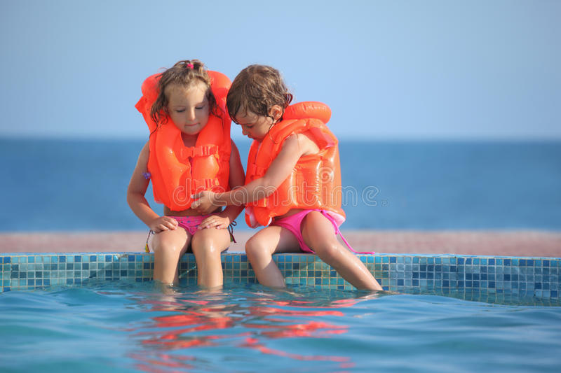 Two Girls In Lifejackets Sitting On Ledge Pool Stock Photography