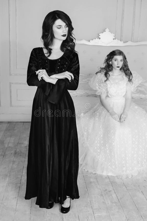 Black and white art monochrome photography. Two girls with long hair in retro dress in the bedroom. Femme fatale in a black dress and nice girl in white wedding stock photo