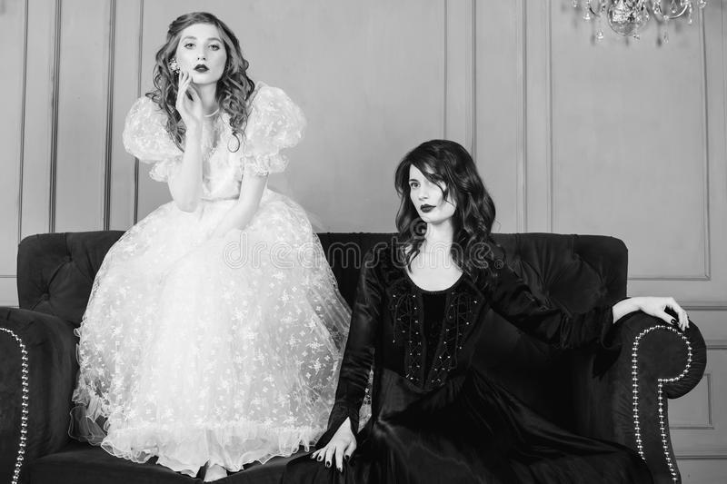 Black and white art monochrome photography. Two girls with long hair in retro dress in the bedroom. Femme fatale in a black dress and nice girl in white wedding royalty free stock photography