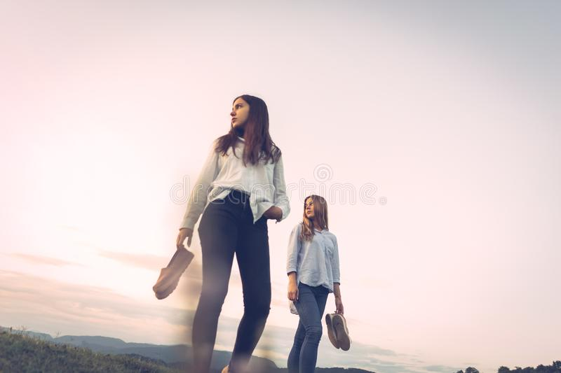 Two girls from a lower angle with shoes in their hands stock image