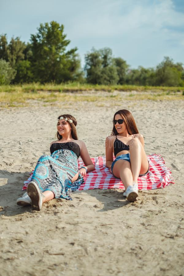 Two girls lying on the beach and smiling royalty free stock photo
