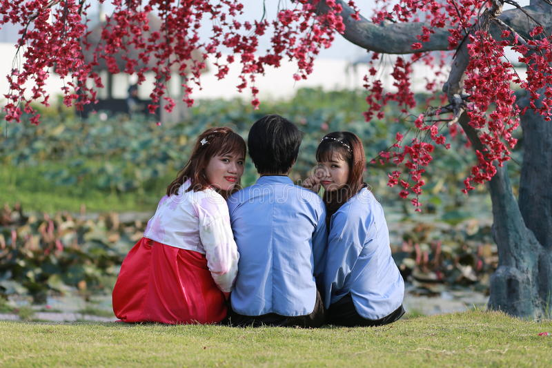 Two girls and a man sitting under a tree royalty free stock photo