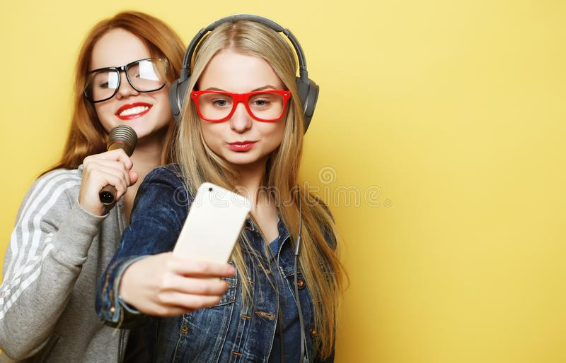 Two  girls with a microphone singing and having fun together, make selfie stock images